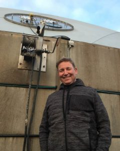 Image shows Happy Days at Ny Rybjerggaard for Jens Henry Christensenat standing beside the reactor.